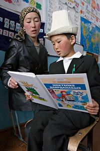 Teacher helping her student read. Satellite Kindergarten (SKG) in Kabylanlal, Kyrgyz Republic.