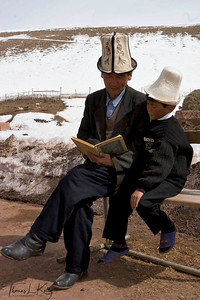 Kyrgyz father read story book to his son. Kyrgyz Republic.