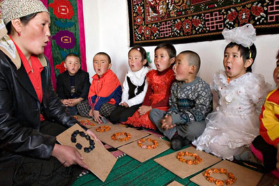 "In Kyrgyz kindergarten, students learn to make alphabets out of coloured lamb-bones. Here they make English alphabet ""O"". Satellite Kindergarten (SKG) in Kabylanlal, Kyrgyz Republic."