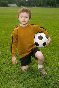 Boy with soccer ball kneeling on a green field