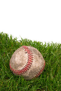 worn,dirty baseball in grass with a white background