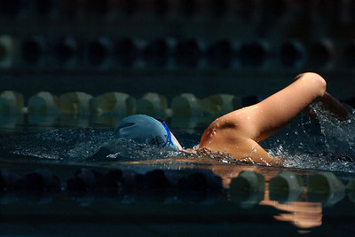 A male swimmer swims the freestyle stroke in a dark pool.