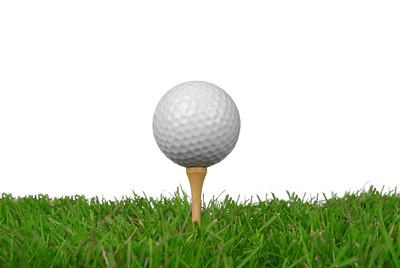 Golf ball close-up from the ground level with grass and white background