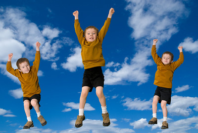 Young attractive boys jumping with a sky background