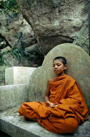 Therevadan Buddhist monks meditating on the monastic surroundings.