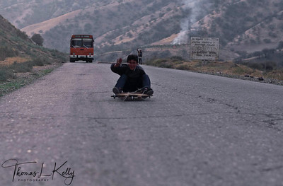 A small boy having some fun by wheeling down-hill a road. Kurgentubee, Tazikistan