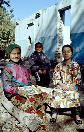 Children sitting outside their school that was destroyed during the war. Kurgentubee, Tazikistan