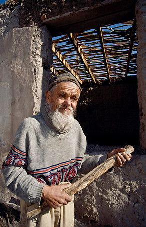 An old man sadly checking his home destroyed in the war. Kurgentubee, Tazikistan