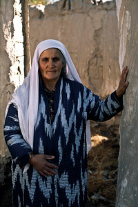 60 Years old Ikromova Kurbonbi is a widow. She lost her husband and 3 sons in the war. Here she stands outside her destroyed home. She now lives with her 12 grandchildren from her 2 sons and her widowed daughter. Her son-in law was also killed in the war. Kurgentubee, Tazikistan