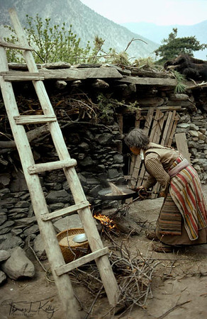 Old Tibetan refugee woman roasting barley at Tseruk resettlement camp, Thak Khola, Nepal