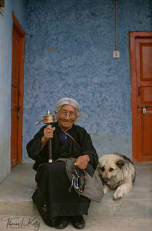 Tibetan grandmother spinning her prayer wheel while her loyal dog beside her. Dharmasala, India