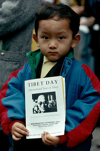 A young Tibetan boy holds pamphlets of Dalai Lama.