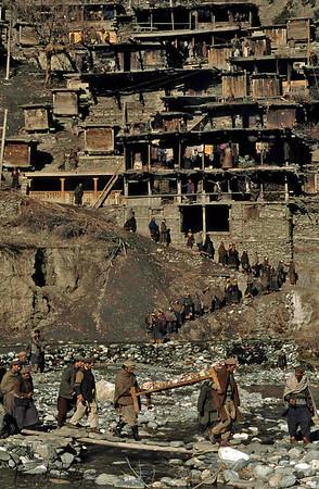 Funeral procession weaves below Rumbir village. The Kalash bury their dead. Chitral, Pakistan.