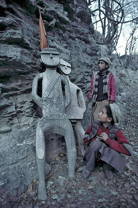 Kalash boys pay homage to the funerary statutes dedicated to the Kalashi ancestors. Chitral, Pakistan.