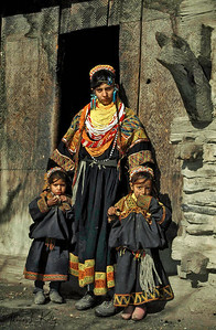 Kalash mother and daughters stand outside the entrance to the sanctuary God Mahandeo at Rumbur village. The horse head symbolizes the presence of the divinity. Chitral, Pakistan.