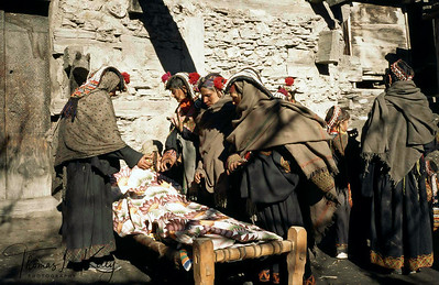 Relatives of the deceased lament and weave their hands above the body so as to assist the soul to detach itself. Chitral, Pakistan.