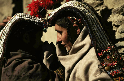 Kalash women participating in Biramor Winter Solstice ceremony in their traditional attire. The kupas, the headdress of the women, is a mark of Kalash identity. Covered with cowrie shells, it is an appeal for protection and fecundity. No women may go bareheaded, without the kupas or at least without the headdress support, the shushut, which is also decorated with cowrie shells, beads, bells, buttons and pompoms. Chitral, Pakistan.