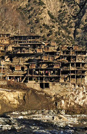 The house of Kalash people are built of timber, the cracks between the logs being filled with mud abd pebbles. In summer the women sit to cook, spin and weave on the wide second-storrey verandah. In winter they cook inside; the smoke escapesthrough the central hole in the cantilevered wooden ceiling. Chitral, Pakistan.