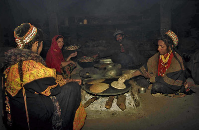 Kalash women preparing bread on metal griddles. Chitral, Pakistan.