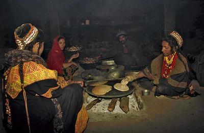 Kalash women preparing bread on metal griddles. Chitral, Pakistan.