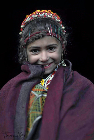 Kalash girl from Rumbir village. Most of the Kalash are pale skinned and some fair hair and blue eyes, all of which give rise to the usual legend that they are descended from the followers of Alexander the Great. Theyare called the Kafir Kalash (Kalash meaning black) because of their women's black robes. Chitral, Pakistan.