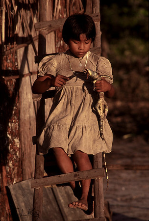 Makuna girl cuts up an iguana for the evening meal.