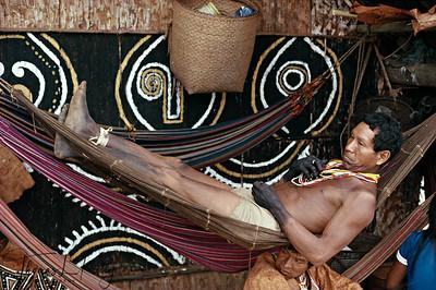 Mankuna man resting in a traditional hammock.