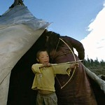 Dukha kid aiming hand mand bow and arrow. West Taiga, Northern Mongolia