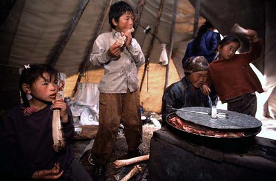 Tsaatan children enjoying eating reindeer bones, inside teepee with their mother. Northern Mongolia