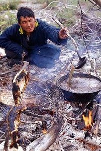 Tsaatan man Cooking fish soup in an open hearth. Northern Mongolia