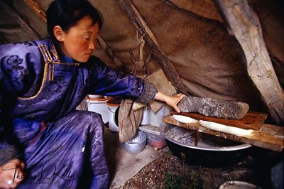 Tssatan woman pressing reindeer cheese between wooden flanks with help of stone, to drain out water from it. Northern Mongolia