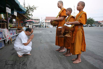 The morning round of alms, where Luang Prabang's monks collects offerings of sticky rice from the laypeople, is a central religious rite of Thevarada Buddhism creating a daily link between the laypeople and those who have chosen monastic life. The monks meditate on emptiness and on the transitory nature of the gifts they receive. Thailand.