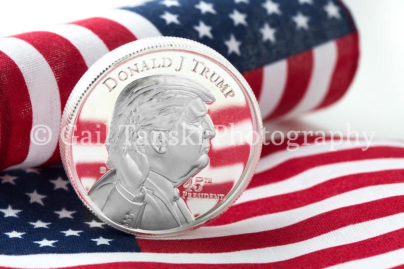 President Donald J Trump silver coin on USA flag background.