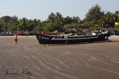 Fishermen push their boats from Aswem beach to Arabian sea to go out for fishing. Ashwem beach is famous for its beach shack and some good accomodation in the form of little resorts. It is also bit unconventional for being rock beach. Goa, India.