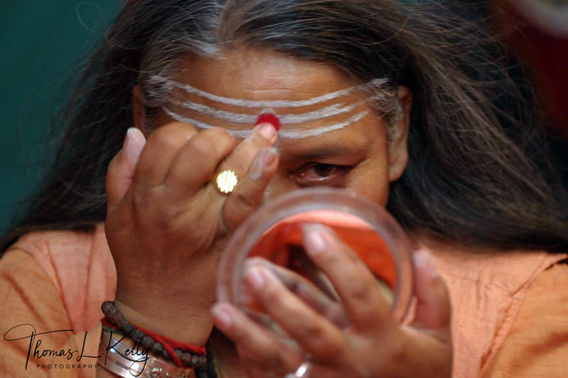 Meera Puri is the leader of the sadhvis (female sadhu), Juna Akhara (followers of Shiva). Meera Puri spent many years practicing her sadhanas in the forest nearby Hrishikesh. She is seen here applying a horizontal forehead decoration called tilaka. Followers of Shiva apply their tilaka by placing three fingers in fire ash and applying in horizontally across the forehead.