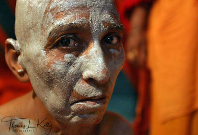 At all Kumbha Melas people from all ages come to be initiated as Sadhus and Sadhvis. The initiation involves a renouncement of all worldly possessions and previous ties. Women take refuge with a particular revered saint; they shave their head, give away their clothes, and receive a new name given by their leader. All other sadhvis within Meera Puri's akhara apply the sacred ash from the dhuni (sacred fireplace) to the new initiate. This is a significant gesture of welcoming and sealing the bond with the individual. Ujjain, India.