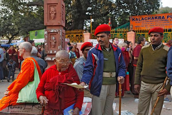 Bihari Policeman help old Tibetan nun with pamplet of Kalachakra initiation. Kalachakra Initiation in Bodhgaya, Bihar, India. (Jan-2012)