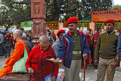 Bihari Policeman help old Tibetan nun with pamplet of Kalachakra initiation. Kalachakra Initiation in Bodhgaya, Bihar, India. (Jan-2012)