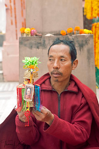 Buddhist monk holding blessed water in a vessel with HH Dalai Lama amulet. Inside Mahabodhi temple. Kalachakra Initiation in Bodhgaya, India. (Jan-2012)