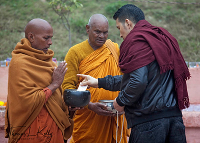 Sri Lankan monks  receiving help from Buddhist pilgrim. Kalachakra Initiation in Bodhgaya, India. (Jan-2012)