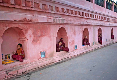 Young monks sit inside wall niche of Maha Bodhi Temple complex and pilgrims make money while circumambulating the temple. Kalachakra Initiation in Bodhgaya, India.