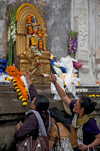 Pilgrims making money, flower and incense offering to Tara. Kalachakra Initiation in Bodhgaya, Bihar, India. (Jan-2012)