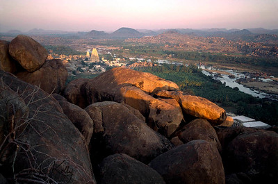 Seen from Matanga Parvatam hill top, the white, 52 meter-tall Virupaksha Temple shimmers in the setting sun.  Virupaksha, considered a manifestation of Shiva, was the family deity of the kings of Vijayanagar and was thus accorded a prime position in their pantheon.  He was also regarded by some to be the Lord of the Nagas or Serpents who support the world and bring the life-giving rain. Hampi, Karnataka, India.