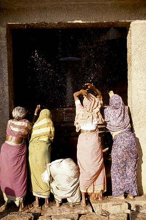 Local village women worship the lingam of Shiva in an ancient shrine. Hampi, Karnataka, India.