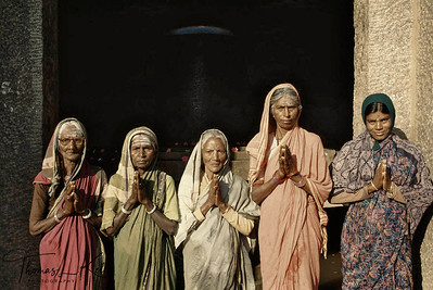 Local village women worship the lingam of Shiva in an ancient shrine. Hampi, Karnataka, India.