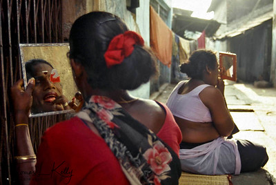 Hijaras getting ready (wearing sari and make up) to be married to the South Indian temple god, in an age-old rite performed by the sweating, topless temple priest, a re-enactment of the marriage of Mohini (a female incarnation of Lord Krishna) and Aravan related in the Hindu mythological epic, Mahabharata.