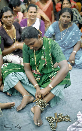 Hijaras tying 'ghungroo' (anklet as seen)  on legs to dance in  Aravan temple festival, south of Chennai (Madras) which attracts hijras (transsexuals) from all over India.