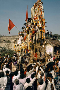 As the chariot of the god Aravan is pulled in procession, shop-keepers and devotees make propitiatory offerings such as flowers, incense and these piles of husked coconuts, offerings of burnt camphor are made to the god Aravan as the deity passes by in procession.The Koothandavar Temple of Aravan is visible in the background.
