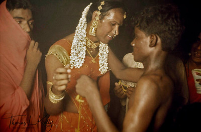 """Bride of Aravan being """"married"""" to the god inside the Koothandavar Temple, the South Indian temple god, in an age-old rite performed by the sweating, topless temple priest, a re-enactment of the marriage of Mohini (a female incarnation of Lord Krishna) and Aravan related in the Hindu mythological epic, Mahabharata. Another hijra (tranny) friend looks on. The marriage lasts for only one festive night then the god is killed in effigy and the brides become wailing widows the next day."""