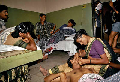 """A hijra plucks the whiskers from her boyfriend's face in the hotel room. Later the couple will get """"married"""" in the temple of Aravan."""